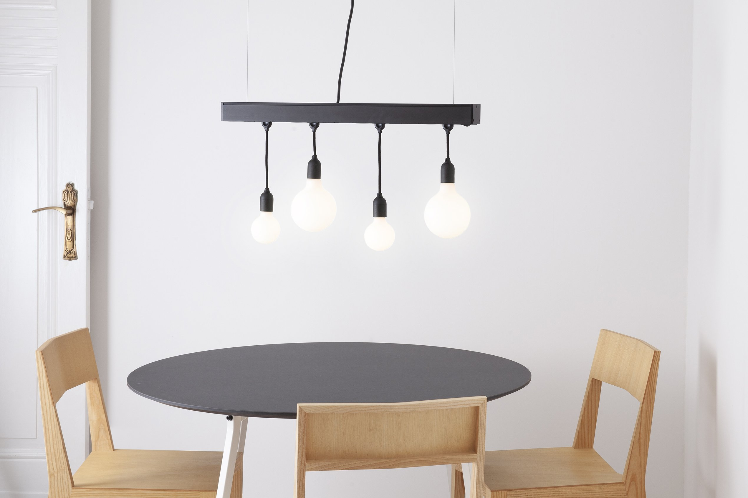 Hang Jack pendant lamp and power bar fitted with LED Porcelain Bulbs (turned on) above an Easy Round Table and Chair 3